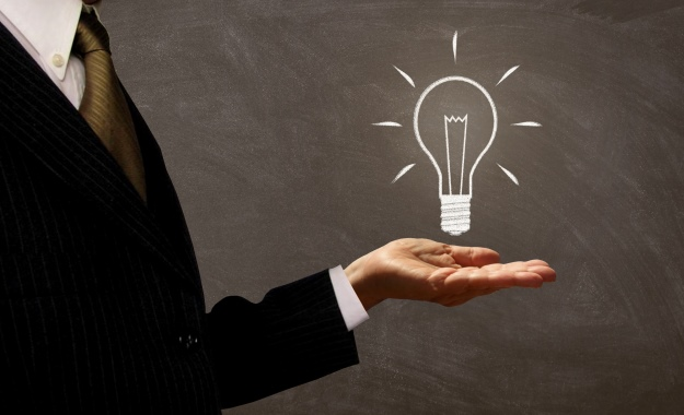 Businessman Holding Light Bulb on Chalkboard